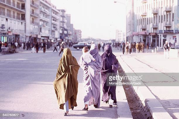 Three women in colorful burkas with covered faces walk down a street their crisp modern slacks and Western style high heel shoes peeking out from...