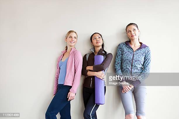 Three women in dance studio standing by wall