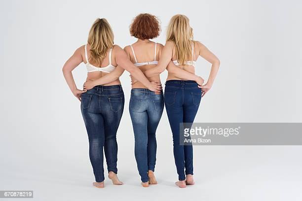 three women in jeans at the studio. debica, poland  - knackiger po stock-fotos und bilder
