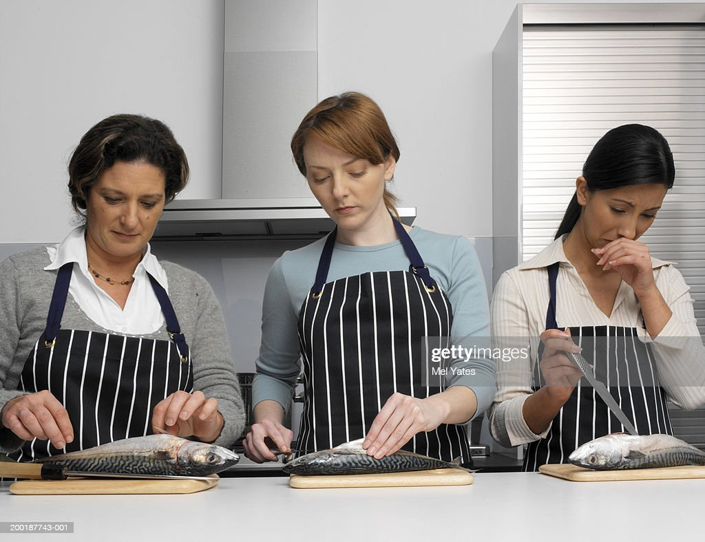 Three women in kitchen gutting fish on chopping boards : Stock Photo