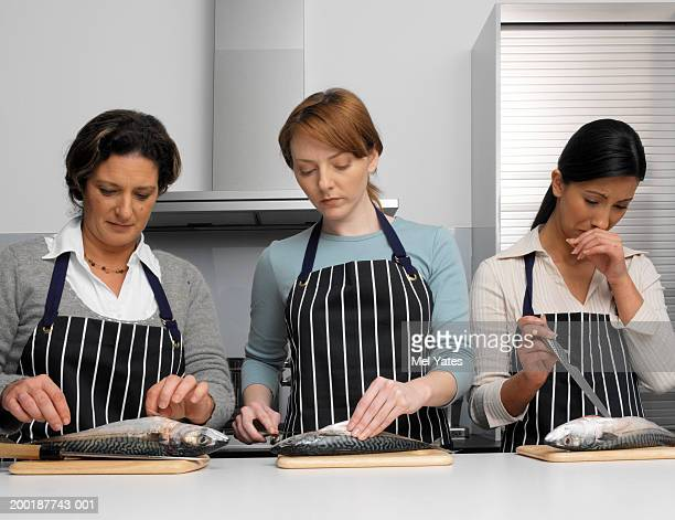 Three women in kitchen gutting fish on chopping boards