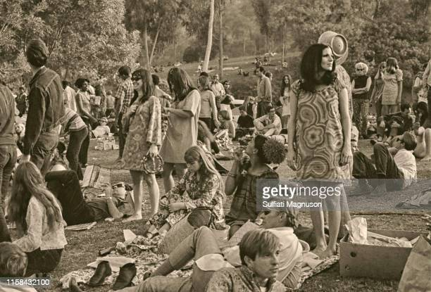 """Three women in """"mod"""" shifts standing, man reading Proust lying on the grass, many people relaxing on the grass at the 1st Elysian Park Love-In on..."""