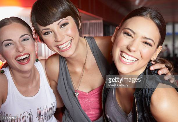 Three women in nightclub having fun and smiling
