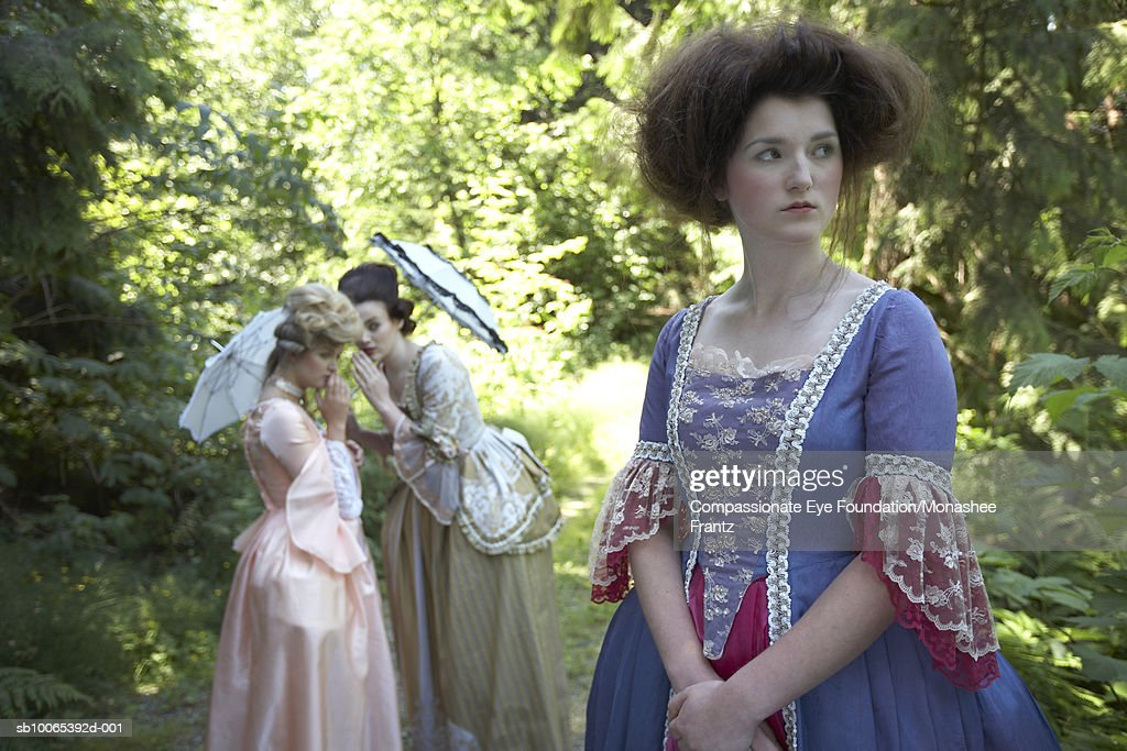 Three women in period dresses, one standing in front of two whispering in background : Foto stock