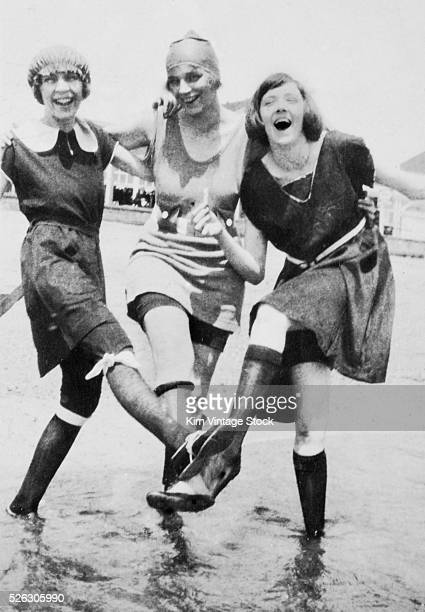 Three women in period swimwear kick up their legs together and laugh while wading in the ocean