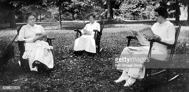 Three women in rocking chairs read magazines ca 1915