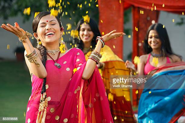 three women in saris, throwing petals
