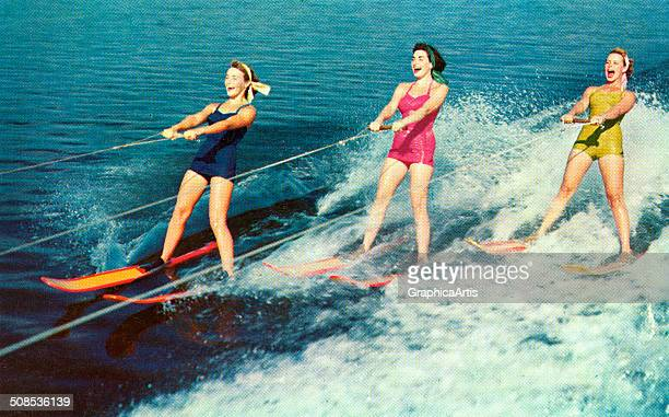 Three women in swimsuits having fun waterskiing c 1955 Screen print from a photograph
