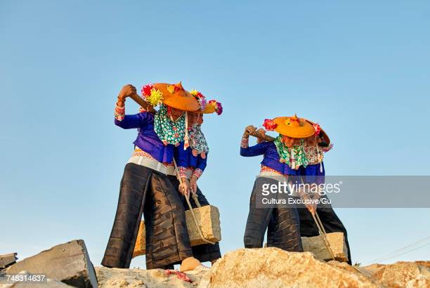 three women in traditional clothes carrying stones in shoulder yokes, dazuo, fujian, china - chapeau chinois photos et images de collection