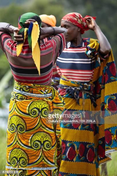 three women in traditional clothing putting on headscarves, masango, cibitoke, burundi, africa - burundi east africa stock pictures, royalty-free photos & images