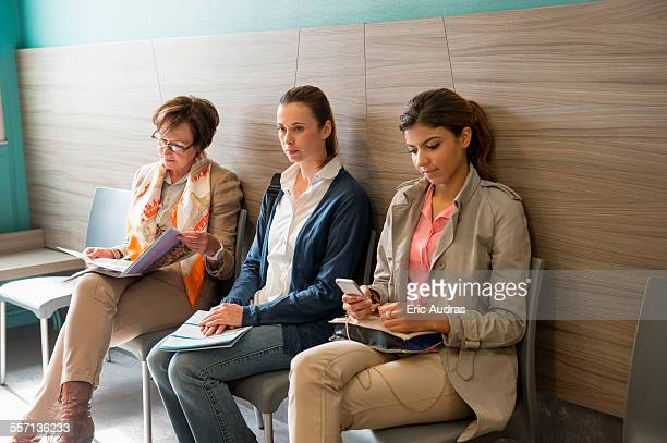 three women in waiting area of hospital - attendre photos et images de collection