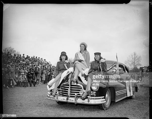 Three women including one in center wearing sash inscribed 'Miss Alpha Phi Alpha' seated on hood of Pontiac car with crowd standing behind wire fence...