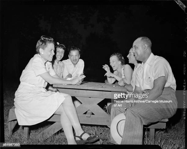 Three women including one on left wearing light colored dress and bun on top of head and three men gathered around picnic table at North Park for...