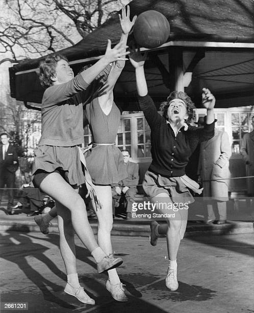 Three women jumping for the ball during a netball match between London Lancashire Insurance and Bensons at Lincoln's Inn Fields
