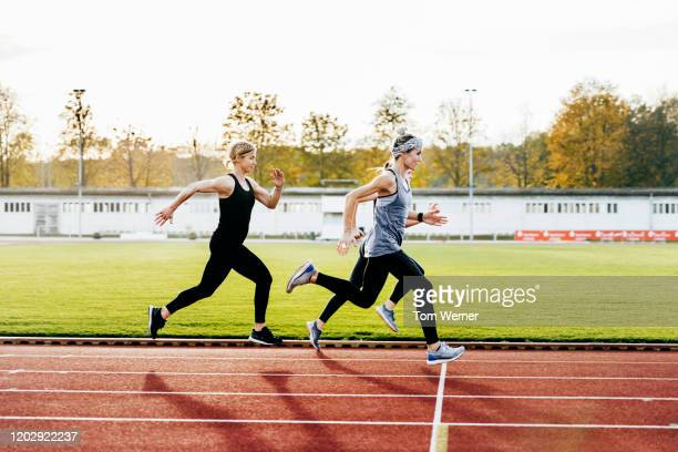 three women keeping healthy running together - track event stock pictures, royalty-free photos & images