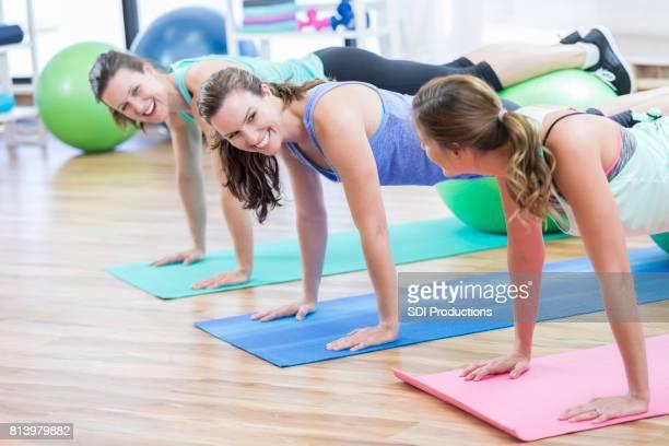 Tres mujeres reír mutuamente durante flexiones en el gimnasio