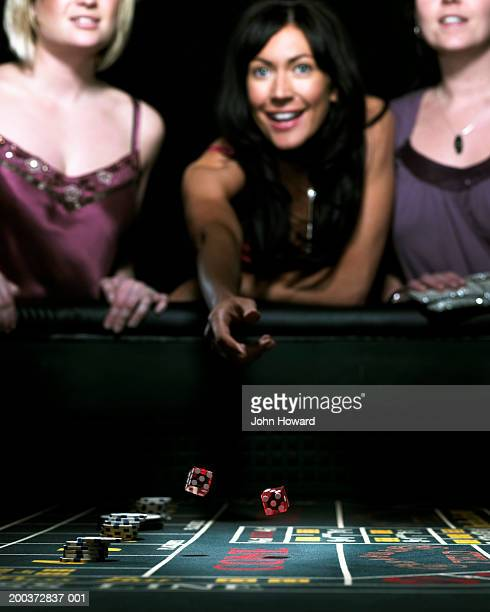 Three women leaning on gaming table one throwing dice, smiling