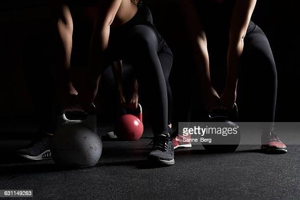 Three women lifting kettle bells in gym