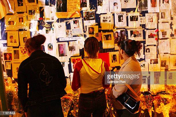 Three women look at flyers of the missing from the World Trade Center disaster at a Prayer Wall September 15, 2001 in New York four days after the...