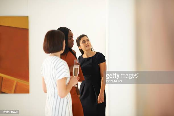 Three women looking at oil paintings at art gallery opening