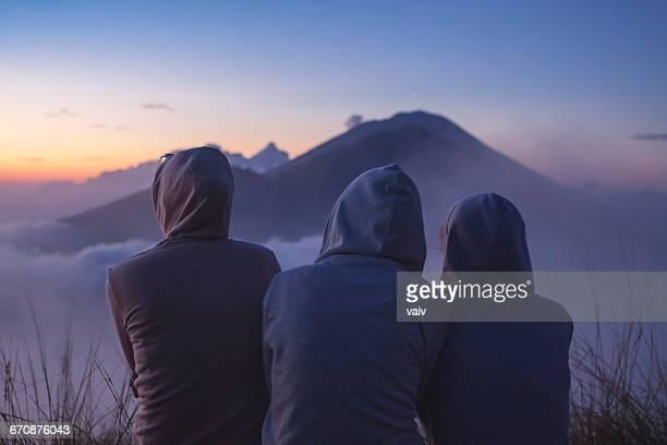Three women looking at sunrise, Mount batur, Bali, Indonesia