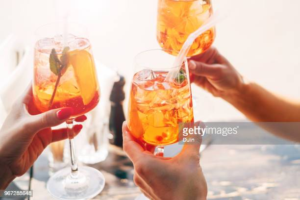 Three women making a celebratory toast with aperol spritz cocktails