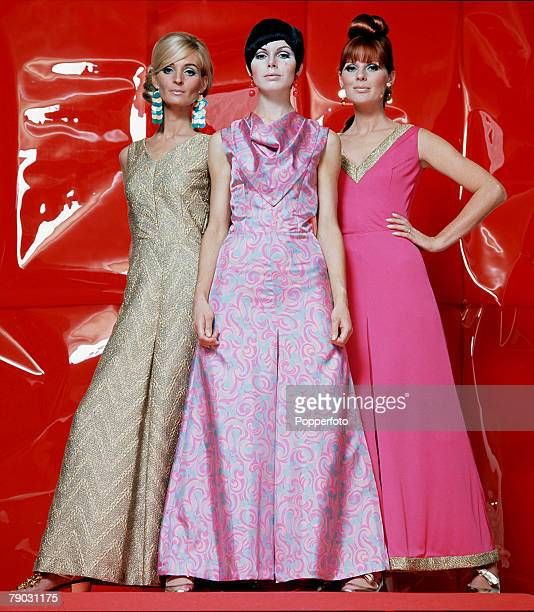 Three women model long evening wear in pinks and gold in an unusual studio setting with a red plastic background 1966