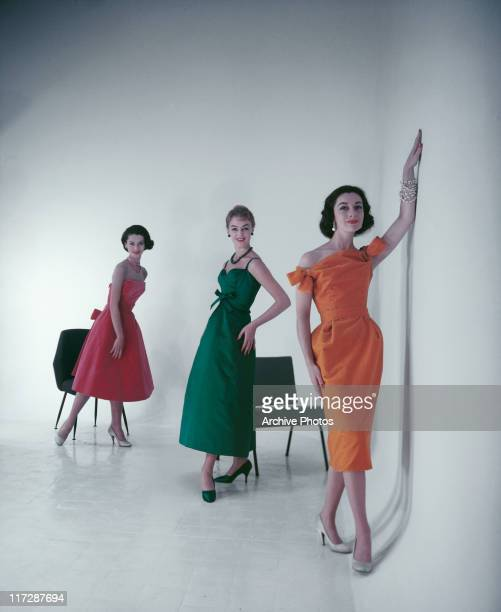 Three women modelling women's fashions in a studio portrait with two in the background posing beside chairs and wearing pink and green dresses with...