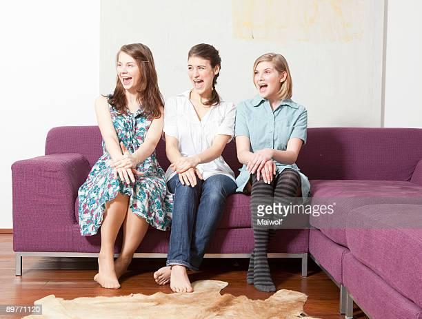 Three women on a sofa, screaming.