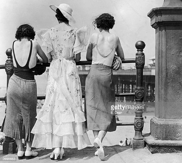 Three women on Blackpool promenade during a heatwave One wears a divided skirt and the other a straight skirt both over swimwear The middle one has a...
