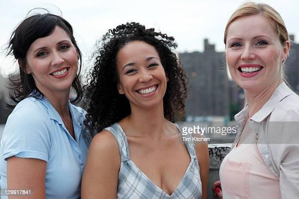 three women on rooftop in city, smiling - alleen mid volwassen vrouwen stockfoto's en -beelden