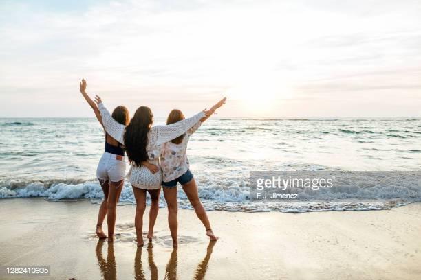 three women on the beach at sunset - group f stockfoto's en -beelden