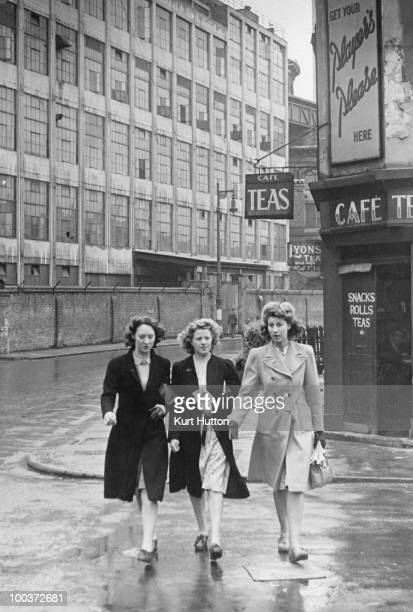Three women on the way from the factory where they work to church where they will pray for their servicemen husbands Battersea London June 1944...