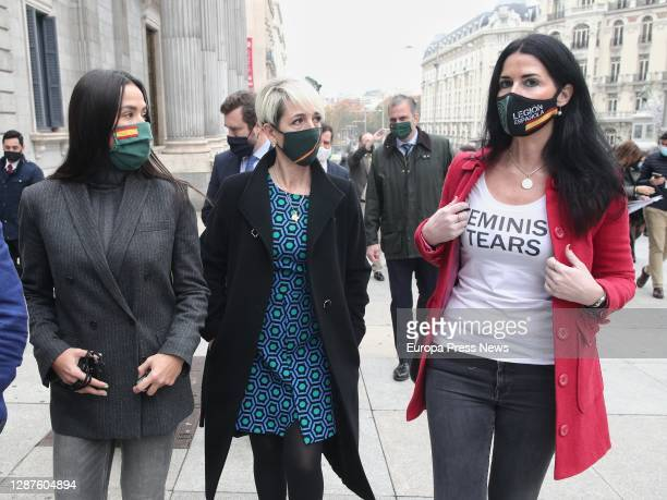"""Three women, one of them wearing a T-shirt that reads """"Feminist Tears"""", participate in an event on the steps of the Congress of Deputies on the..."""