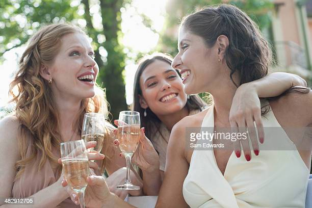 Three women outdoors at a party with champagne smiling