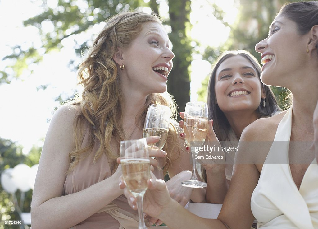 Three women outdoors at a party with champagne smiling : Stock Photo