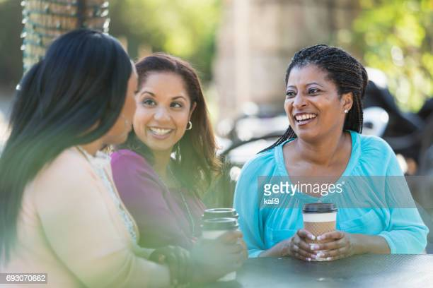 Three women outdoors talking, drinking coffee