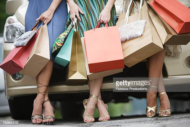 three women outdoors with shopping bags leaning on car - shopping bag stock pictures, royalty-free photos & images