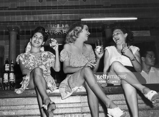 Three women perched on the bar at the Cabaret Kursal nightclub in Havana Cuba circa 1950