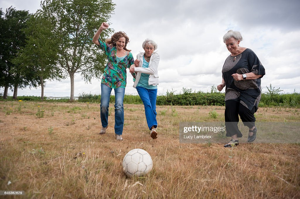 Three women playing soccer outdoors : Stockfoto