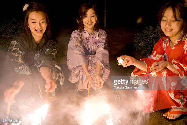 Three women playing with sparklers at night