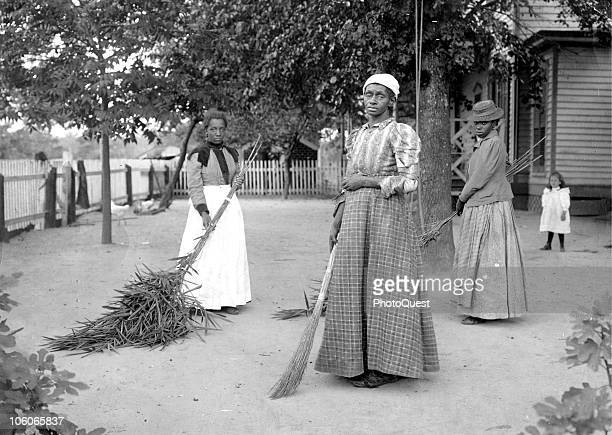 Three women pose with brooms in the dirt yard of a house Belton South Carolina mid to late 19th century A young girl stands in the background