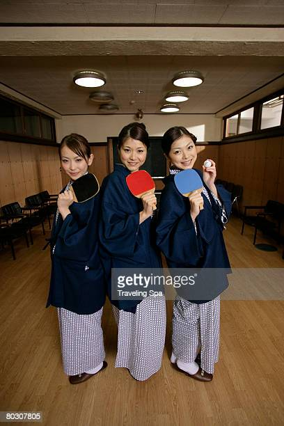 Three women posing with table tennis bat