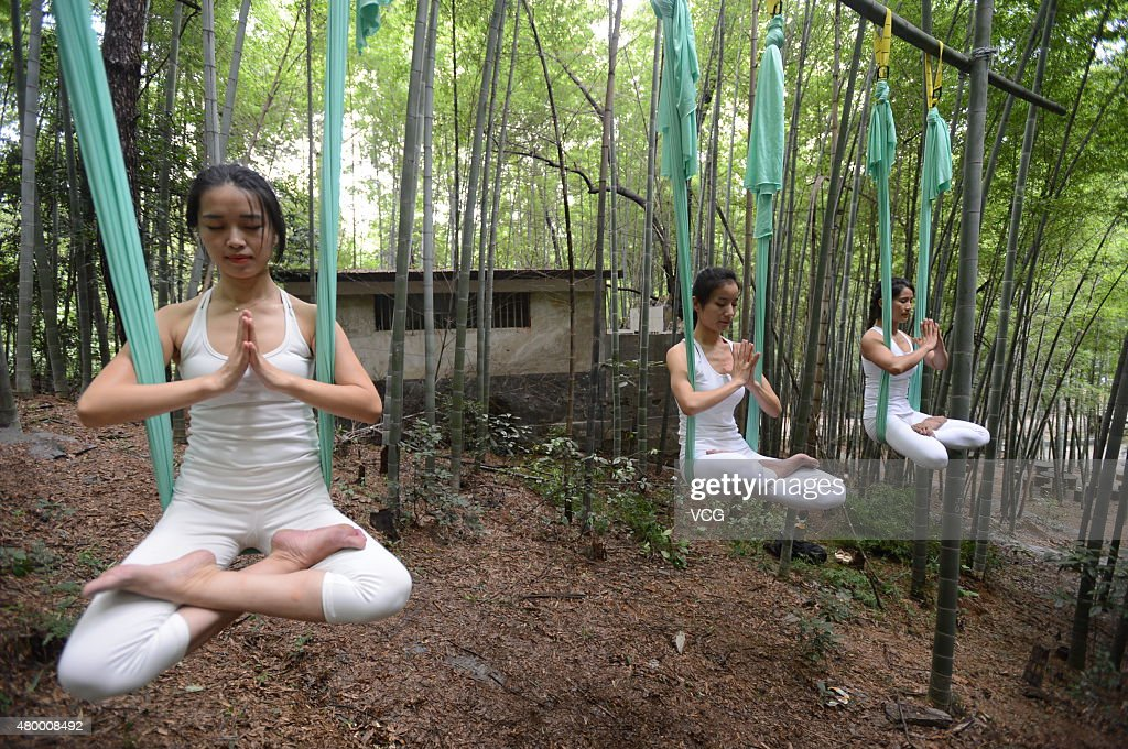 Three women practice yoga with hammock and hang in the air in the bamboo forest on July 4, 2015 in Changsha, China.