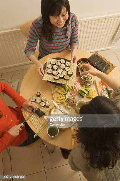 Three women preparing sushi at table, elevated view