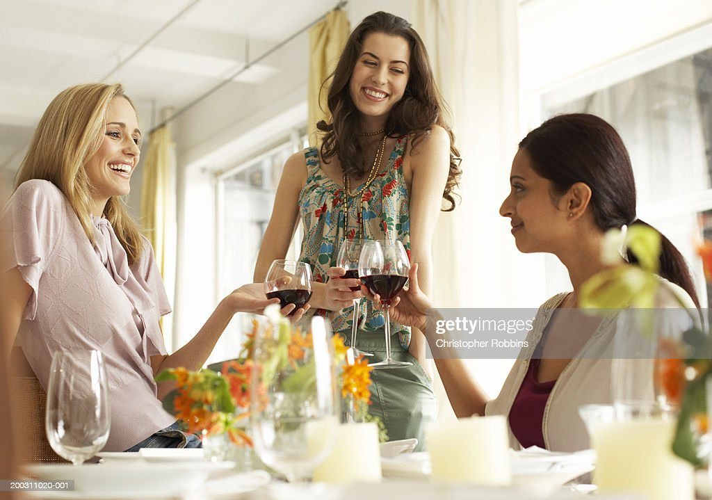 Three women raising glasses of red wine at dinner party, smiling : Stock Photo