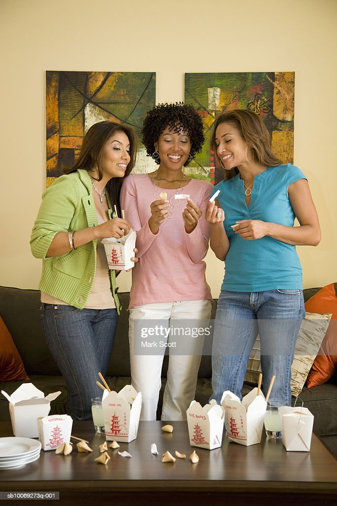 Three women reading fortune cookie messages in living room : Stockfoto