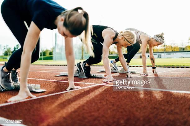 three women ready at starting blocks on outdoor running track - 女子トラック競技 ストックフォトと画像