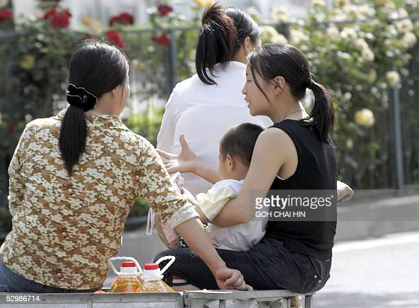 Three women ride on a tricycle with a child after shopping at a supermarket in Beijing 27 May 2005 China's one child birth control policy coupled...