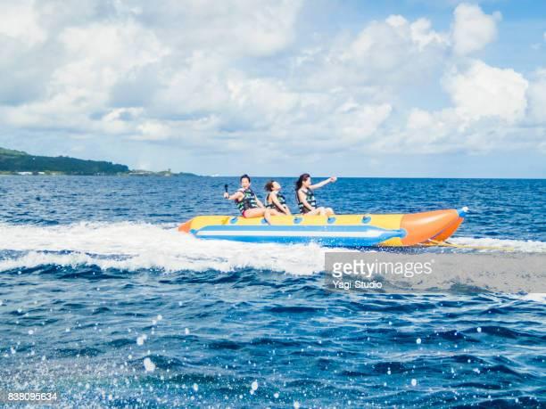 Three women riding a banana boat in guam